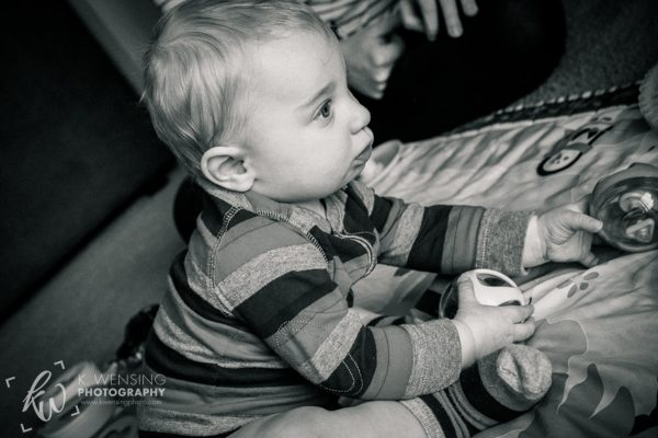 Black and white photo of playing baby.