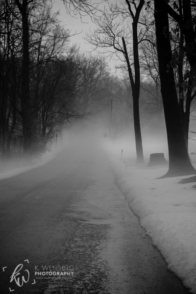 Black and white photo of misty road.