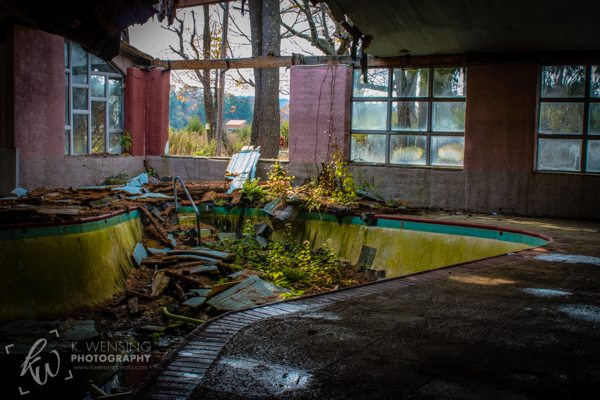 A collapsed ceiling above an empty swimming pool.
