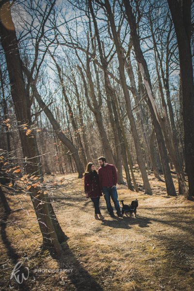 Engaged couple walking their pup in the woods.