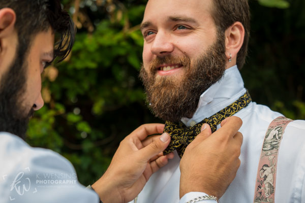 Groomsman helping the groom with his bow tie.