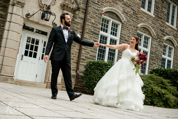 Wedded couple playfully dancing around at Penn State University.