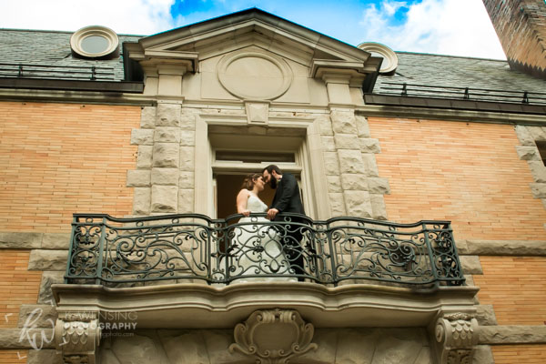 Bride and groom standing upon balcony.