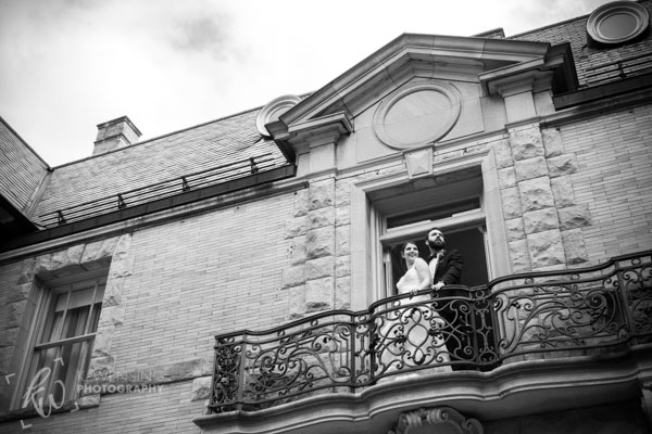 Smiling couple standing out on a balcony.