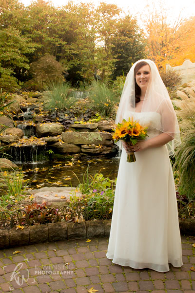 The beautiful bride posing near the pond.