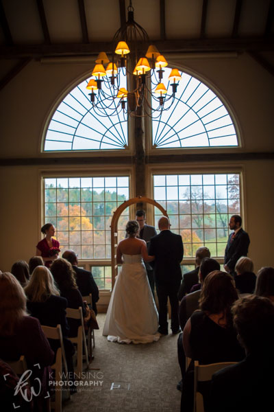 Indoor wedding ceremony with a Fall backdrop.